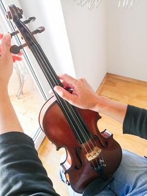 楽器を膝の上に置いて指で弦をはじきながらするチューニング